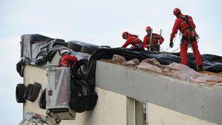 Des pompiers en intervention sur un toit deBourcefranc-le-Chapus (Charente-Maritime), dimanche 5 février. (XAVIER LEOTY / AFP)