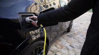 Une personne recharge son véhicule électrique, en octobre 2019 à Paris. (ALEXIS SCIARD / MAXPPP)
