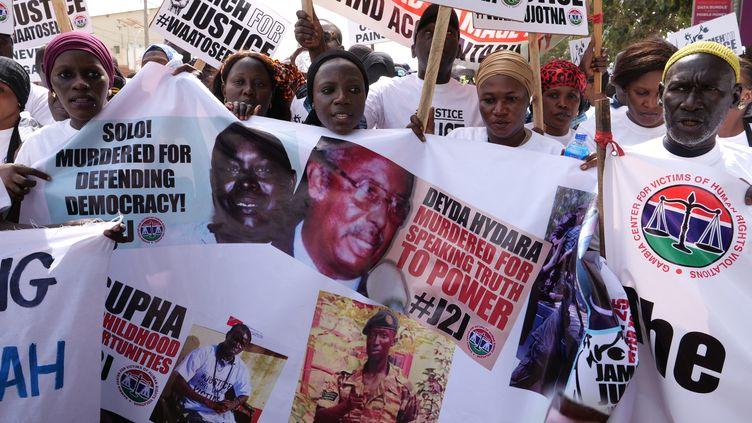Des manifestants brandissent les visages de victimes du régime de Yahya Jammeh, l'ancien président de la Gambie, lors d'une manifestation demandant qu'il soit traduit en justice à Banjul, la capitale gambienne, le 25 janvier 2020. (ROMAIN CHANSON / AFP)