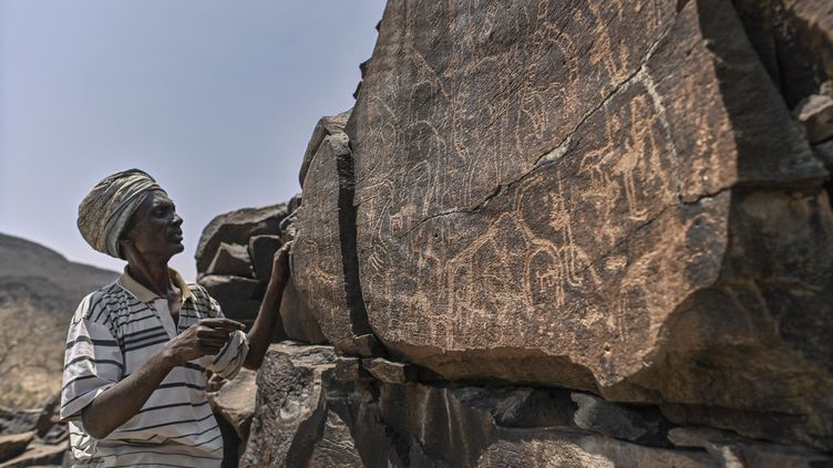 Ibrahim Dabale, 50 ans, autochtone et gardien de l'art, raconte les anciennes représentations de la faune et d'autres pratiques culturelles, caractéristiques de l'époque, gravées dans la roche volcanique sur le site d'art rupestre d'Abourma au nord de Djibouti. (TONY KARUMBA / AFP)