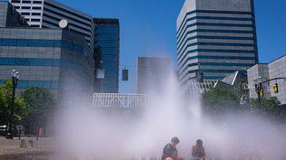 A Portland (Oregon), dans le nord-ouest des Etats-Unis, des jeunes serafraîchissent dans une fontaine alors que la région connaît une vague dechaleur sans précédent, dimanche 27 juin. (NATHAN HOWARD / GETTY IMAGES NORTH AMERICA / AFP)