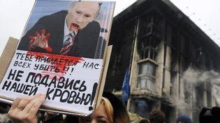 Une manifestante arbore une affiche hostile à Vladimir Poutine, le 2 mars 2014 à Kiev (Ukraine). (YURIY DYACHYSHYN / AFP)