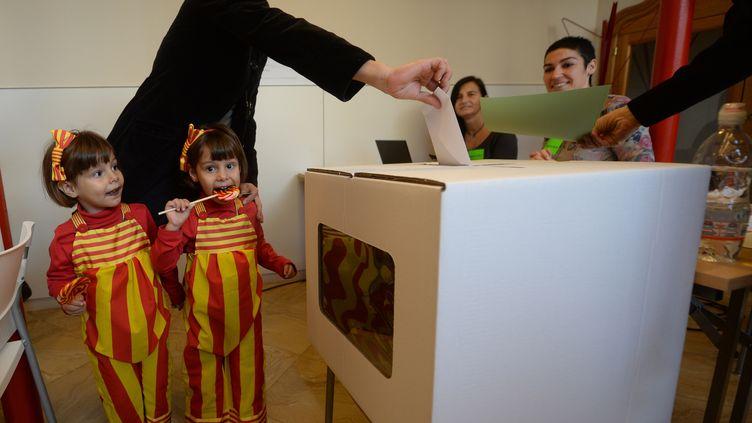 Une femme, accompagnée de ses filles habillées aux couleurs de la Catalogne, participe au processus participatif sur l'indépendance de la Catalogne, dimanche 9 novembre, à Barcelone (Espagne). (EVRIM AYDIN / ANADOLU AGENCY / AFP)