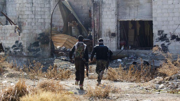 Les rebelles de l'Armée syrienne libre courent se couvrir dansDaraya bombardée, une banlieue Damas le 15 janvier 2014 (REUTERS )
