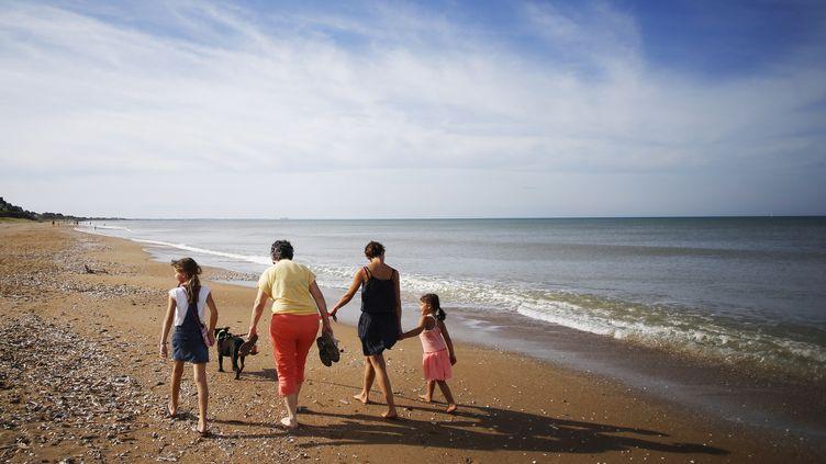 Une famille se balade sur la plage de Cabourg (Calvados), le 13 octobre 2018. (CHARLY TRIBALLEAU / AFP)