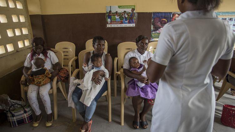 Une infirmière explique les moyens de protéger les enfants contre le paludisme et les performances du vaccin RTS,S à la polyclinique Ewin de Cape Coast au Ghana, le 30 avril 2019. (CRISTINA ALDEHUELA / AFP)