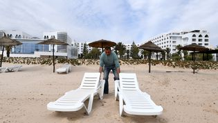 Un employé de l'Imperial Merhaba Hotelde Port El-Kantaoui dispose des chaises longues sur la plage, le 21 avril 2017, à Sousse (Tunisie). (FETHI BELAID / AFP)