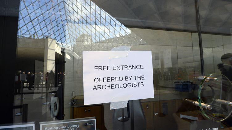 """""""Entrée gratuite, offerte par les archéologues"""", signale cette affiche scotchée au musée du Louvre, à Paris, le 5 février 2015. (BERTRAND GUAY / AFP)"""