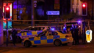 Des véhicules de police près de la Manchester Arena, une salle de concert au Royaume-Uni où une explosion a fait plusieurs morts, le 22 mai 2017. (PAUL ELLIS / AFP)