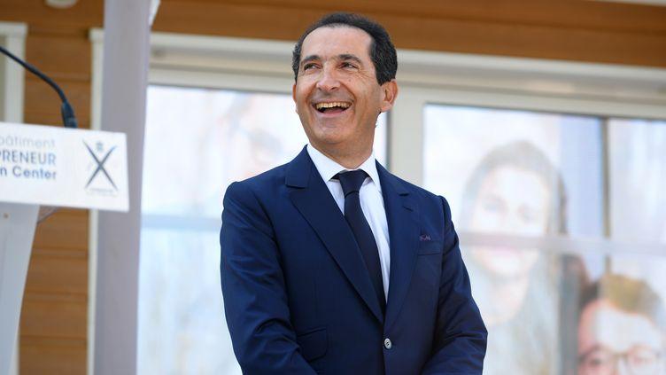 """Le président du groupe Altice, Patrick Drahi, sourit en assistant à l'inauguration du centre d'innovation """"Drahi -X"""" à l'école Polytechnique, à Palaiseau (Essonne), le 19 avril 2016. (ERIC PIERMONT / AFP)"""