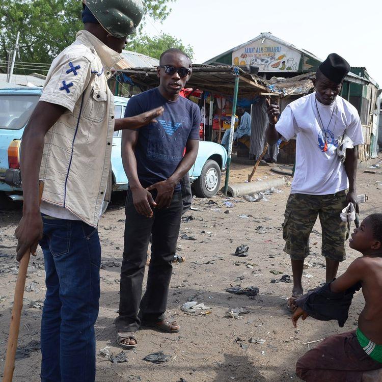 Des membres des milices civiles interrogent une personne suspectée d'appartenir à Boko Haram, à Maiduguri, dans le nord du Nigeria. (AMINU ABUBAKAR / AFP)