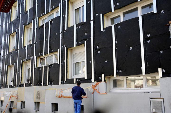Un ouvrier installe des panneaux d'isolant sur la façade d'un immeuble à Nantes (Loire-Atlantique), le 25 mars 2013. (ALAIN LE BOT / AFP)