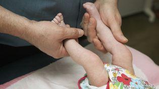 Un ostéopathe tient les jambes d'un enfant d'un mois, en 2012. (HUMBERT / BSIP / AFP)