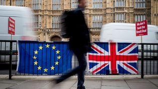 Un homme passe devant le Parlement britannique, à Londres, le 4 mars 2019. (TOLGA AKMEN / AFP)