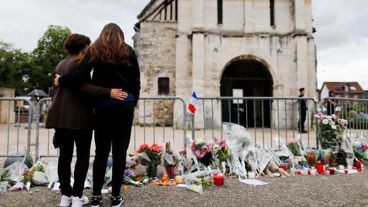 Fleurs et recueillements, le 27 juillet 2016, devant l'église de Saint-Etienne-du-Rouvray, près de Rouen en Normandie, au lendemain de l'égorgement du prêtre Jacques Hamel par deux djihadistes. Un crime aussitôt revendiqué par l'organisation de l'Etat islamique. (CHARLY TRIBALLEAU/AFP)