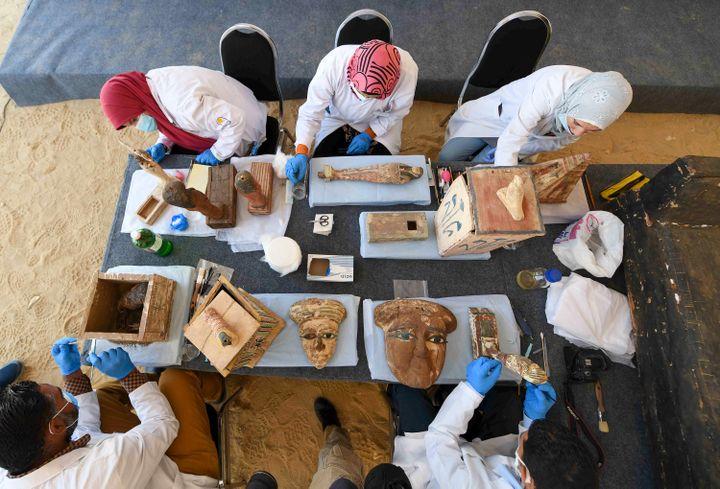 Des archéologues nettoient des statues et masques funéraires à l'occasion de la présentation de la centaine de sarcophages, le 14 novembre 2020 à Saqqara (AHMED HASAN / AFP)