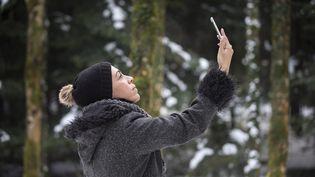 Une femme prend une photo avec son téléphone portable, dans une forêt suisse, le 21 décembre 2017. (BRIGITTE BLÄTTLER / MOMENT RF / GETTY IMAGES)