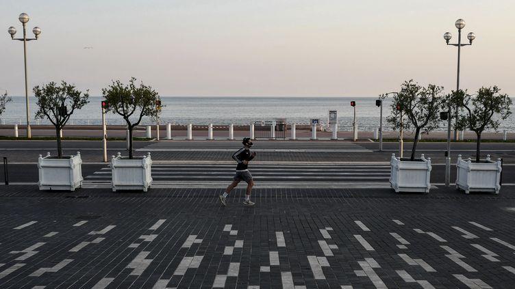 Un homme fait son jogging devant la Promenade des anglais dans la ville de Nice, le 3 avril 2020. (VALERY HACHE / AFP)