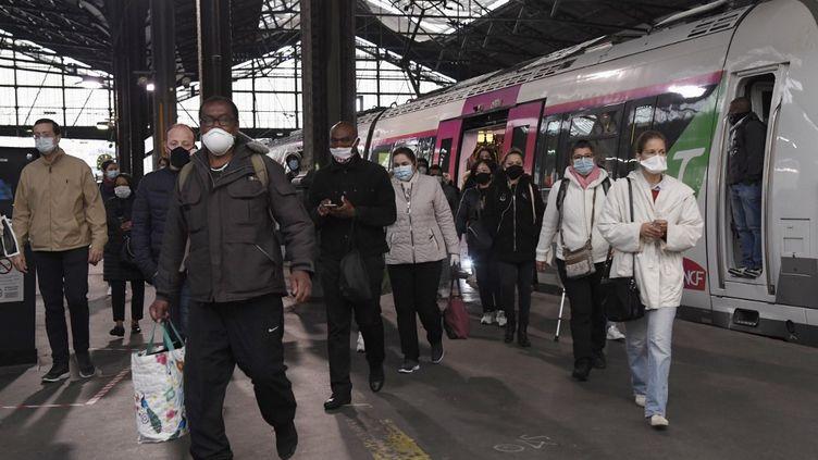 Des voyageurs à la gare Saint-Lazare, à Paris, le 11 mai 2020. (BERTRAND GUAY / AFP)