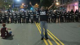 Ken Nwadike entre les manifestants et les forces de l'ordre à Charlotte, en Caroline du Nord (Etats-Unis), mercredi 21 septembre 2016. (FREE HUGS PROJECT / YOUTUBE)