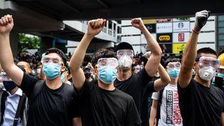 Des manifestants se protègent avec des masques et des lunettes, alors que la police a fait usage de gaz lacrymogène mercredi. (PHILIP FONG / AFP)