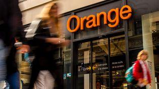 Des piétons passent devant une boutique de l'opérateur téléphonique Orange à Lille (Nord). (PHILIPPE HUGUEN / AFP)