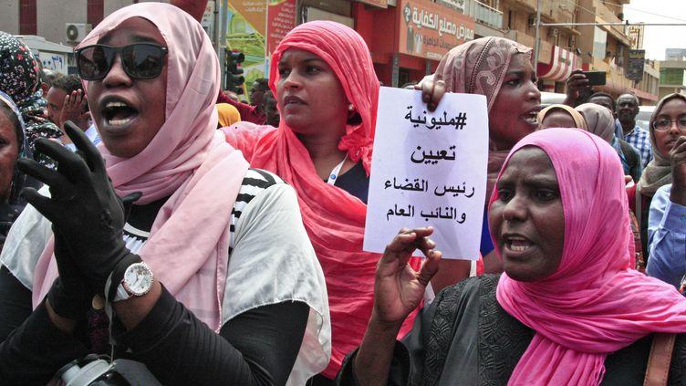 """Lors d'une manifestation de masse le 12 septembre 2019 près du palais présidentiel à Khartoum, des femmes brandissent une pancarte sur laquelle on peut lire """"un million de manifestants vont nommer le nouveau chef de l'appareil judiciaire et un nouveau procureur général"""". (EBRAHIM HAMID / AFP)"""