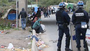 Des policiers casqués surveillent un camp de migrants, après des bagarres, à Calais (Pas-de-Calais), le 22 septembre 2015. (MAXPPP)