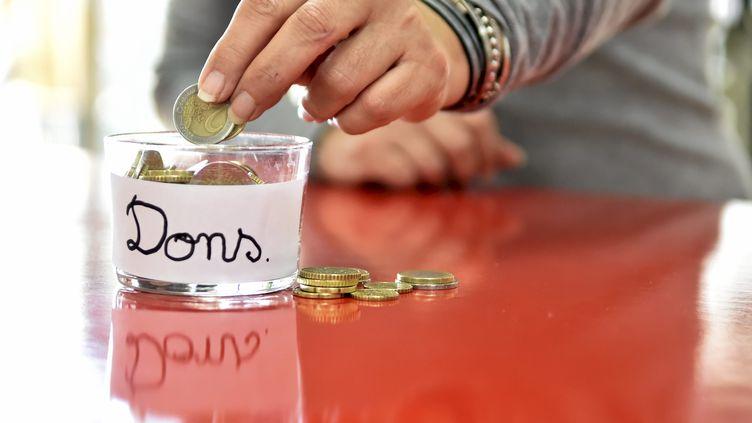 Un homme fait un don de pièces de monnaie. Photo d'illustration. (SYLVIE CAMBON / MAXPPP)