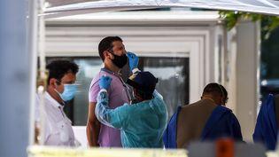 Un soignant prélève des échantillons sur un homme dans un centre de dépistagedu Sars-CoV-2à Miami (Floride), le 24 juin 2020. (CHANDAN KHANNA / AFP)
