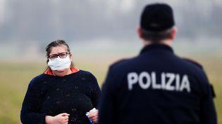 Une habitante de Casalpusterlengo au sud de Milan. la ville a été mise à l'isolement pour cause de multiplication de cas de coronavirus Covid-19. (MIGUEL MEDINA / AFP)