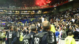 Des policiers regardent les pétards allumés dans les tribunes du Parc OL, à Lyon, le 13 avril 2017. (RICHARD MOUILLAUD / MAXPPP)