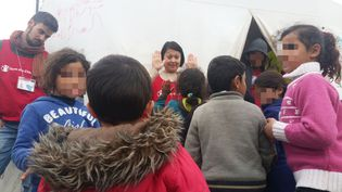 Une volontaire de l'ONG Save The Children joue avec des enfants au camp de migrants d'Idomeni (Grèe), le 16 mars 2016. (LOUIS SAN / FRANCETV INFO)