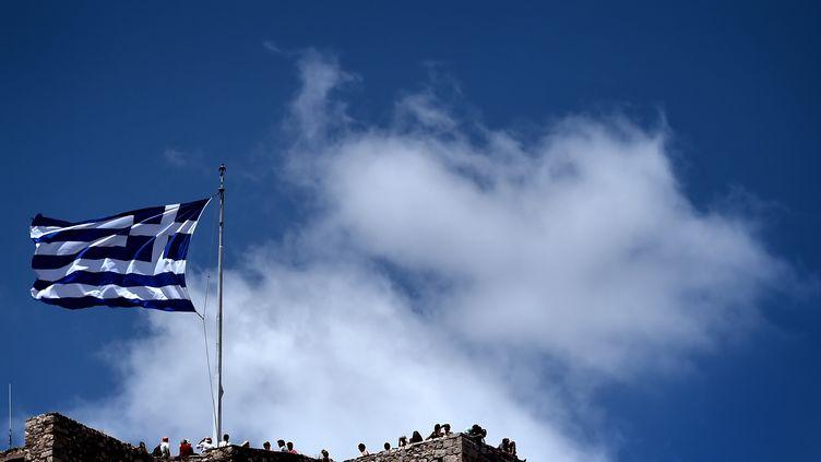 Un drapeau grec flotte à Athènes (Grèce), le 5 juillet 2015. (ARIS MESSINIS / AFP)