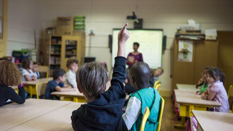 Un élève lève la main dans une école parisienne, en 2014. (FRED DUFOUR / AFP)