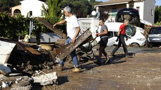 Des habitants de Biot (Alpes-Maritimes) nettoient leur quartier après des inondations le 4 octobre 2015. (JEAN-CHRISTOPHE MAGNENET / AFP)