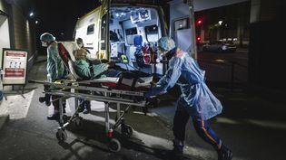 Des soignants transportent un homme dans un hôpital parisien, le 3 avril 2020. (LUCAS BARIOULET / AFP)