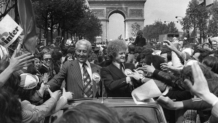 Le président du club de Saint-Etienne Roger Rocher et l'entraineur de l'équipe première Robert Herbin signent des autographes sur les Champs-Elysées, le 13 mai 1975. (STF / AFP)