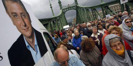 Des partisans de l'ancien Premier ministre (ex-PC) Ferenc Gyucsany en train de l'écouter le 14 septembre 2013 pendant une manifestation sur le pont de la Liberté à Budapest, à côté d'une affiche représentant l'homme politique. (AFP - Ferenc Isza )