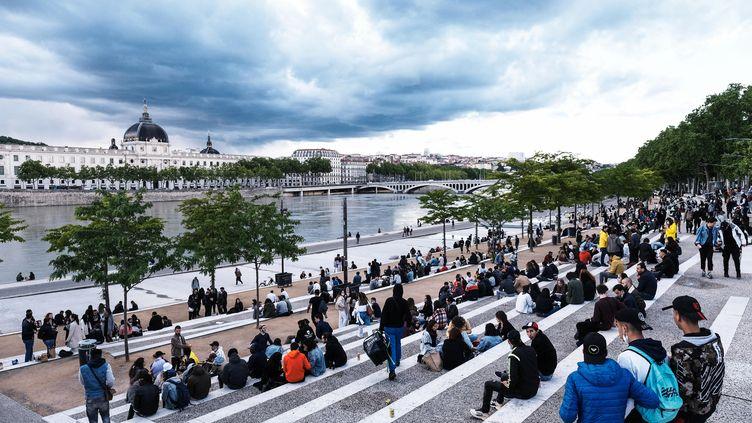 Des promeneurs s'installent sur les bords du Rhône lors du déconfinement à Lyon, le 19 mai 2021. (ANTOINE MERLET / HANS LUCAS)