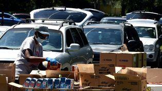 Un volontaire distribue des colis de nourriture à Orlando en Floride, le 7 août 2020. (PAUL HENNESSY / NURPHOTO / AFP)