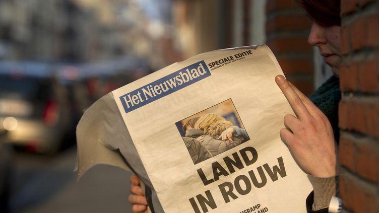 Une femme lit l'édition spéciale d'un journal flamand à Heverlee (Belgique), le 14 mars 2012, après la mort de 28 personnes dont 22 enfants dans un accident de car en Suisse. (CHRISTOPHE KETELS / BELGA)