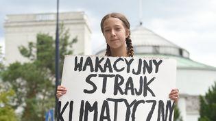 La militante polonaise Inga Zasowska tient une pancarteappelant à faire grève pour le climat pendant les vacances, le 28 juin 2019 à Varsovie. (JANEK SKARZYNSKI / AFP)
