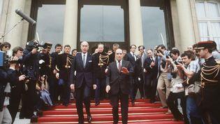 Le nouveau président français, François Mitterrand raccompagne son prédécesseur Valéry Giscard d'Estaing dans la cour de l'Elysée, le 21 mai 1981à Paris, à l'issue de la cérémonie de passation de pouvoir. (STF / AFP)