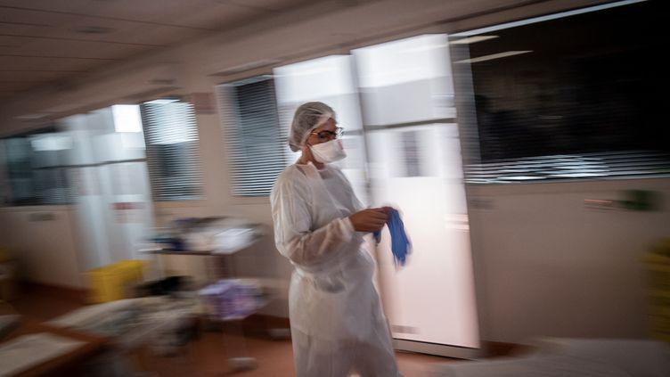 Une soignante enfile ses protections avant de s'occuper depatients infectés par le Covid-19 dans un service de réanimation à Vanves. Phto d'illustration. (LOIC VENANCE / AFP)