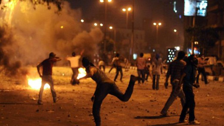 Des manifestants en train de jeter des pierres au Caire contre la police après l'attaque de l'ambassade israélienne (AFP - MOHAMED HOSSAM)