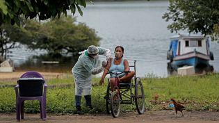 Un employé du ministère de la Santé vaccine une femme au Brésil, le 14 février 2021. (TARSO SARRAF / AFP)