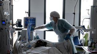 Un membre du personnel médical s'occupe d'un patient Covid-19 sous assistance respiratoire, dans une chambre du service de réanimation du centre hospitalier universitaire (CHU) Pierre Zobda-Quitman de Fort-de-France, sur l'île française de la Martinique, dans les Caraïbes, le 29 août 2021. (ALAIN JOCARD / AFP)