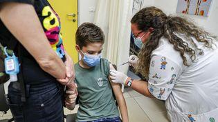 Un enfant reçoit une injection d'un vaccin contre le Covid-19 à Holon, en Israël, le 21 juin 2021. (JACK GUEZ / AFP)