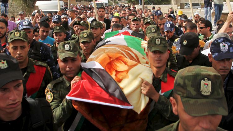Les membres des forces nationales de sécurité palestiniennes portent le corps de Riham Dawabsheh, à Douma, enCisjordanie,le 7 septembre 2015. (ABED OMAR QUSINI / REUTERS)